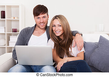 Happy young couple using computer at home - Happy young...