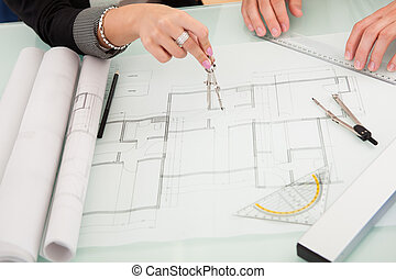 Architects discussing blueprints - Cropped overhead view of...