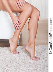 Woman stroking her bare legs - Cropped view image of a young...