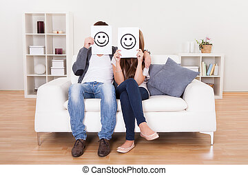 Couple covered faces with smiley white paper