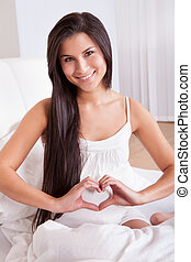 Pregnant woman making a heart sign - Beautiful smiling...