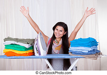 The ironing is finished - Happy woman throws her arms in the...