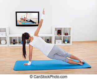 Woman practicing yoga at home standing on a mat on her...