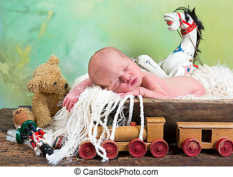 Old toys and newborn baby - Newborn baby sleeping in a...