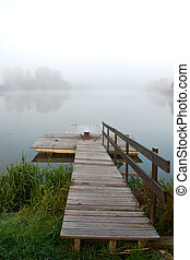 Footbridge and lake in fog