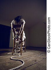 Woman prisoner - Young woman tied to a chair in a empty room