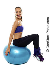 Pretty lady sitting on big blue exercise ball. Casual studio...