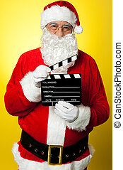 Cheerful Kris Kringle posing with clapperboard - Its time...