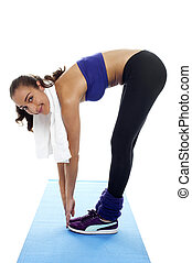 Fit woman bending over and touching her toes. Facing the...