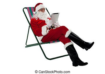 Kris Kringle relaxing and using electronic tablet - Kris...