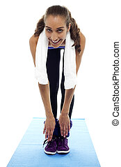 Flexible woman bending down till toes isolated against white...