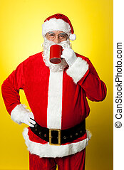 Portrait of a aged Santa sipping coffee