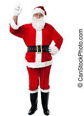 Bespectacled Santa pointing upwards