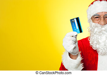Cropped image of aged Santa holding credit card