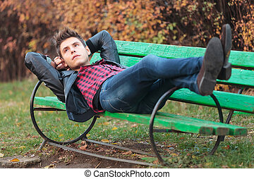 casual man resting on a bench in the park