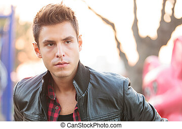Young casual man with leather jacket looking away from the...