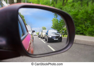 reflection in an automobile mirror - car and the road the...