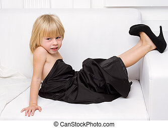 little girl trying on the big shoes - Girl 3 years old in...