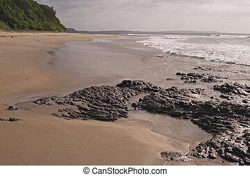Wet rocks in sunlight - Black rocks and foam of breaking...