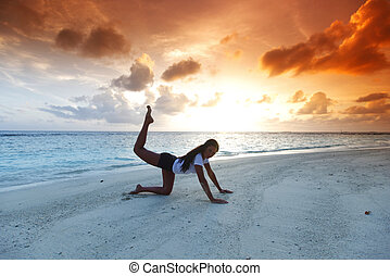 Yoga woman on beach at sunset