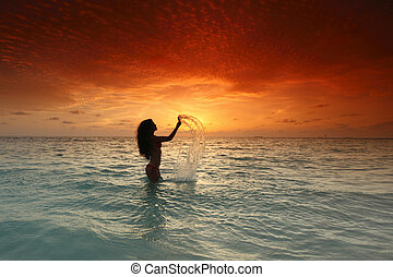Woman in sea on sunset