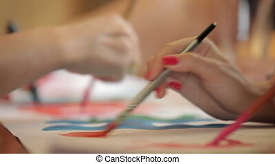 Art classes - People painting an image with watercolors at...