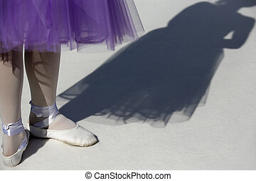 Ballerina in pointe shoes with shadow