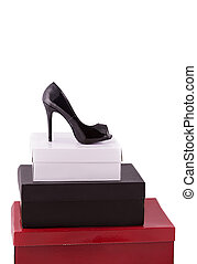 High-heeled black shoe on some boxes over white