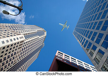 Jet Above Buildings - Corporate jet flying high above...