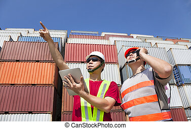 two workers with tablet pc and standing before stack of...