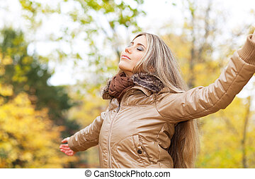 Serene autumn woman - Young woman opening her arms and...