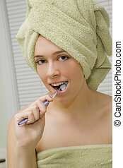 Teenager - Caucasian teenager brushing her teeth wearing a...