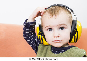 young child on couch with earmuffs - young child on couch...