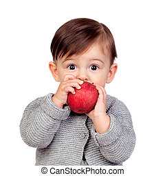 Adorable baby girl eating a red apple isolated on white...