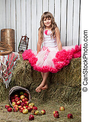 Portrait of funny girl near pail with apples in hayloft -...
