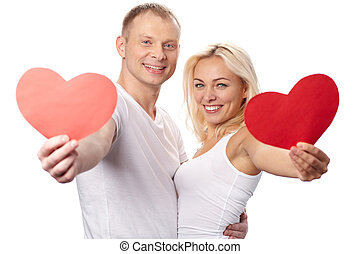 Sweethearts - Portrait of happy couple showing red paper...
