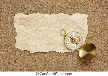Compass on old sheet paper against the background of sand -...