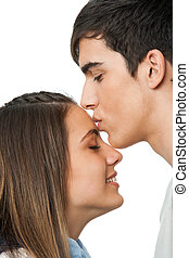 Boy kissing girlfriend on forehead - Close up of boy kissing...