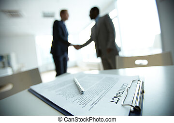 Deal - Image of business contract on background of two...