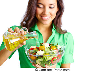 Making salad - Close-up of pretty girl pouring oil into...