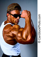 A young and fit male model posing his muscles.On a gray...