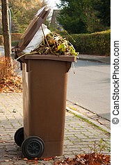 Garbage bin - Overflowing brown garbage bin or can full with...