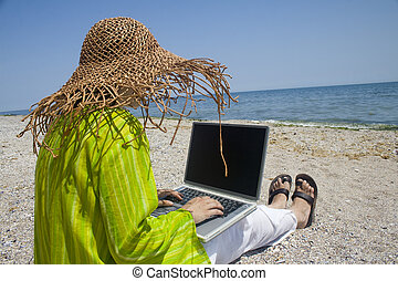 Woman with laptop - Woman in hat sitting on beach working on...