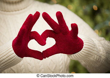 Woman Wearing Red Mittens Holding Out a Heart Hand Sign -...