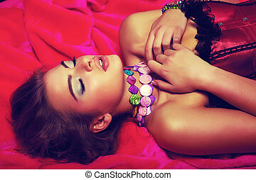 Dreamy sensual romantic girl in red dress lying in bed -...