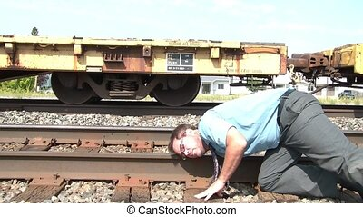 Businessman Puts Ear to Railroad Track - Businessman in...