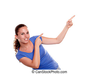 Smiling young woman pointing to her left up