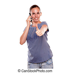 Positive young woman speaking on mobile phone standing over...