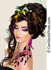 Woman beautiful face with bright makeup and feathers - painted skin