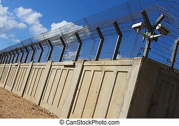 A secured industrial zone with concrete fence on the blue...